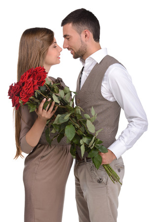 Attractive young loving couple looking at each other and holding a bunch of red roses against white background photo