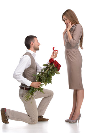 Young man in full suit standing on one knee and making a proposal to his girlfriend against white background photo