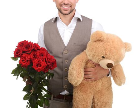 Young man holding a stuffed toy and roses, a gift for the woman I love. Isolated on white background photo