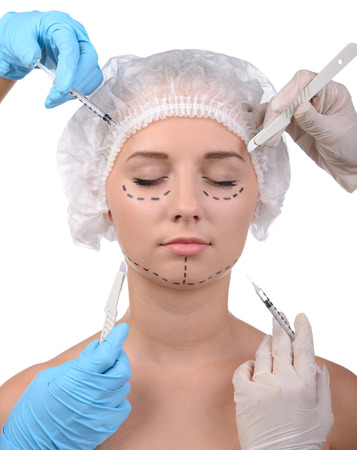 scalpels: Plastic surgery. Terrified young woman looking away while many hands holding syringes and scalpels near her face