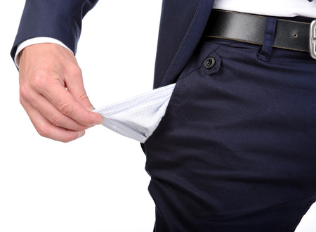 Businessman standing isolated on the white background and showing his empty pocket, turning his pocket inside out, no money Standard-Bild