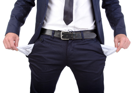 Businessman standing isolated on the white background and showing his empty pocket, turning his pocket inside out, no money Фото со стока