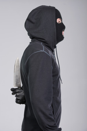hijacker: Masked man aims with knife. on gray background