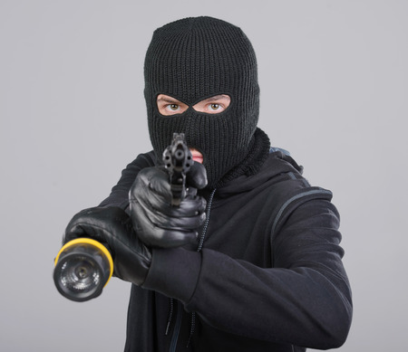 hijacker: Masked robber with gun aiming into the camera against a black background