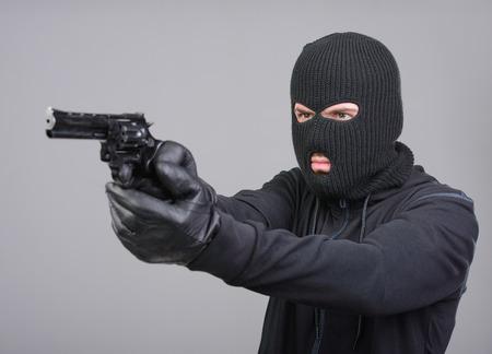Gemaskerde overvaller met een pistool gericht in de camera tegen een zwarte achtergrond
