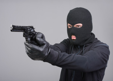 Masked robber with gun aiming into the camera against a black background