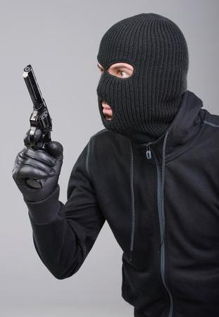 黒い背景に対してカメラに銃を目指しての覆面をした強盗