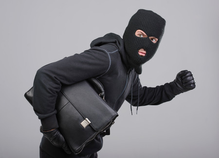 Portrait of running male burglar with a handbag. Isolated on gray