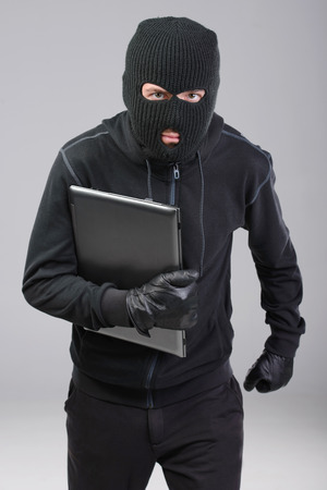 loot: Thief stealing a laptop computer. Isolated on gray