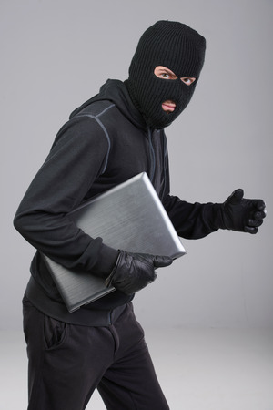 furtive: Thief stealing a laptop computer. Isolated on gray