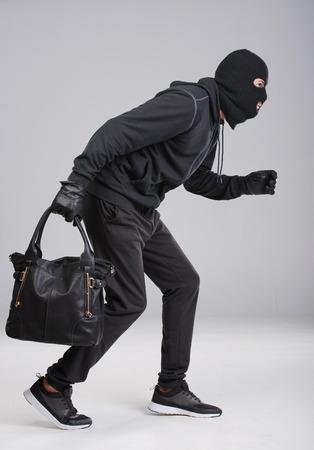 Portret van het runnen van mannelijke inbreker met een handtas. Geïsoleerd op grijs Stockfoto