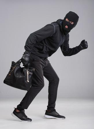 snatch: Portrait of running male burglar with a handbag. Isolated on gray