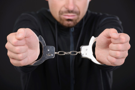 Busted burglar. Angry burglar in handcuffs grimacing at camera while standing against black  photo