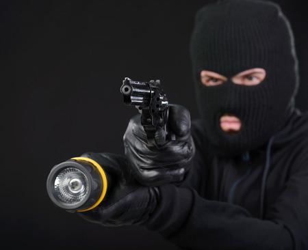 黒に対してカメラに銃を目指すと覆面をした強盗