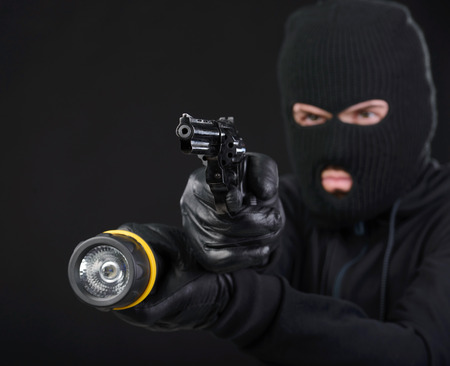 Masked robber with gun aiming into the camera against a black