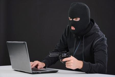 criminal activity: Computer hacking. Close-up of frustrated criminal using computer