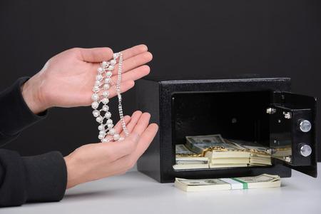 housebreaking: Thief burglar stealing money during home safe codebreaking