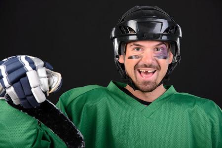 Grappig hockey speler lachend, blauwe plekken rond de ogen.
