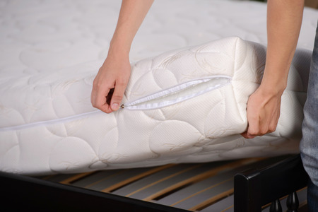 Demonstration of quality. A young man holding demonstrations quality mattress in the bedroom Stock Photo