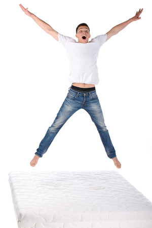 マットレスの上にジャンプ。若い男のマットレス、白い背景で隔離の上ジャンプ