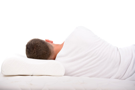 Orthopedic mattress. A young man sleeping on a mattress, side view. Isolated on white background Stock Photo