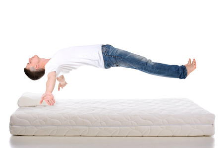 beds: Orthopedic mattress. A young man sleeping on a mattress, side view. Flying during sleep Isolated on white background