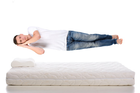 bedding indoors: Orthopedic mattress. A young man sleeping on a mattress, side view. Flying during sleep Isolated on white background