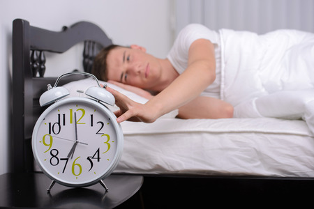 obudził: Exhausted man being awakened by an alarm clock in his bedroom