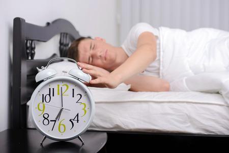 obudził: Wyczerpany człowiek budzi się budzika w sypialni