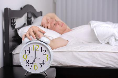 obudził: Wyczerpany człowiek jest obudzony przez budzik w sypialni