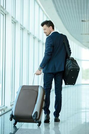 スーツケースを引っ張ってくると、パスポートと航空券をお持ちのビジネス旅行者 写真素材