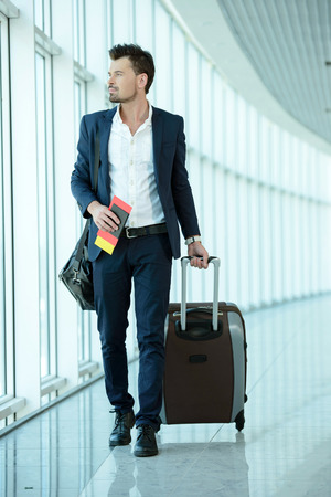 Business traveler pulling suitcase and holding passport and airline ticket Archivio Fotografico