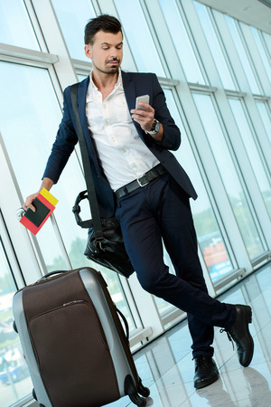 Business man talking on phone traveling walking inside in airport. Casual young businessman wearing suit jacket and shoulder bag. photo