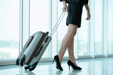 Business woman traveling with trolley. Womens legs, close-up Stock Photo
