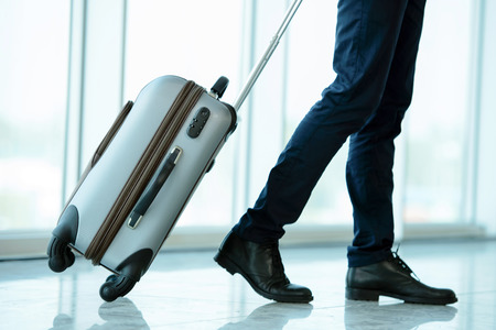 Business traveler pulling suitcase and holding passport and airline ticket Stok Fotoğraf