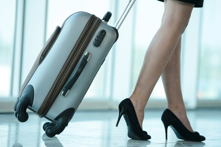 travellers: Business woman traveling with trolley. Womens legs, close-up Stock Photo