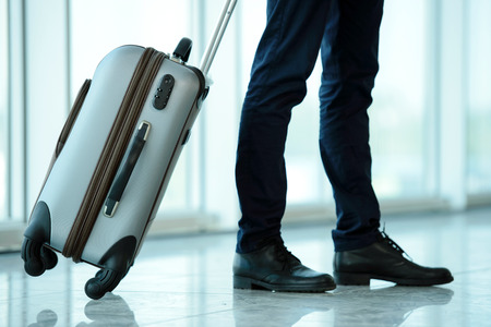 business traveler: Business traveler pulling suitcase and holding passport and airline ticket Stock Photo