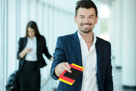 airport check in counter: Businessman handing over air ticket in airport check in counter Stock Photo