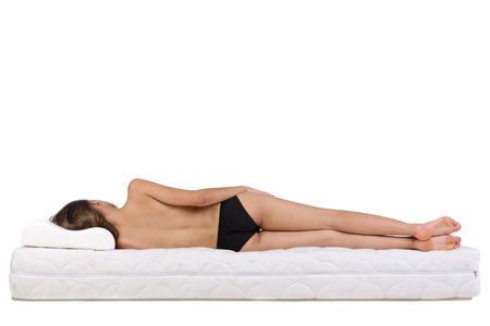 lit: Portrait d'une femme couch�e sur un matelas. Matelas orthop�dique.