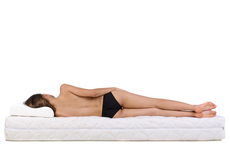 bedding: Portrait of a woman lying on a mattress. Orthopedic mattress.
