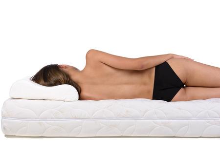 white bed: Portrait of a woman lying on a mattress. Orthopedic mattress.