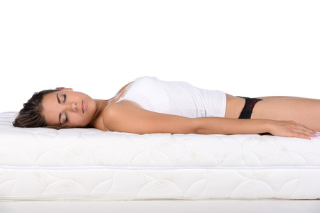 lying in bed: Portrait of a woman lying on a mattress. Orthopedic mattress.