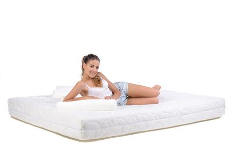 Portret van een vrouw liggend op een matras. Orthopedisch matras. Stockfoto