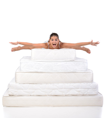 Portrait of a woman lying on many mattresses. Orthopedic mattress. Stock Photo