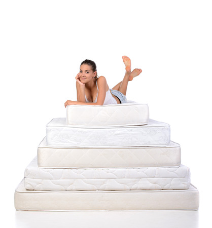 Portrait of a woman lying on many mattresses. Orthopedic mattress. 스톡 콘텐츠