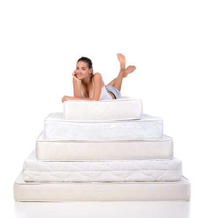 Portret van een vrouw liggend op vele matrassen. Orthopedisch matras. Stockfoto