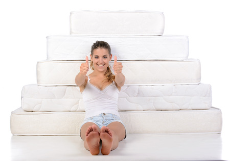 Portrait of a woman sitting near many mattresses. Orthopedic mattress.