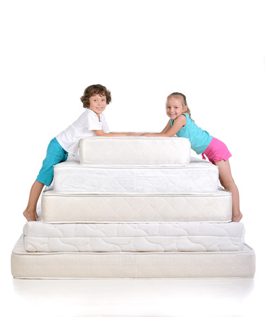 Young children sitting on lots of mattresses, isolated on white background photo