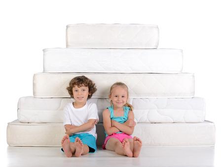 Jonge kinderen zitten op veel matrassen, geïsoleerd op een witte achtergrond Stockfoto
