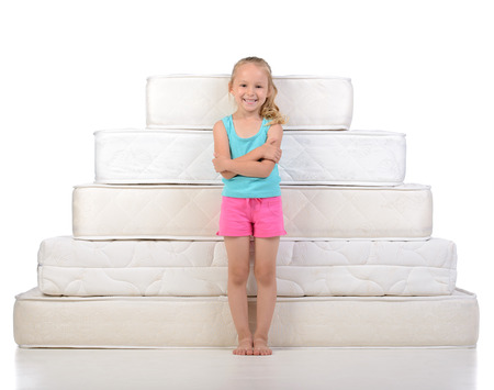 Little girl sitting on a lot of mattresses, isolated on white background